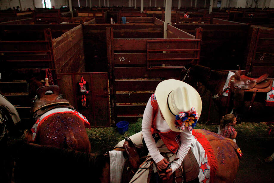 Maddie McClay withe the Flying Fillies Drill Team checks her gear before her teams competes in The Grand National Drill Team Jackpot at the Cow Palace. Photo: Mike Kepka, The Chronicle / ONLINE_YES
