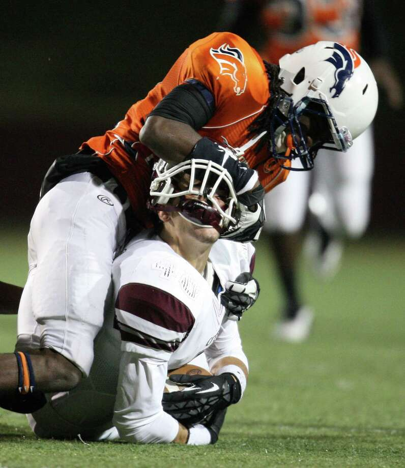 Clear Creek's Kurtis Lester has his helmet rearranged on a tackle by Bush's Jyren McCain in the first half of Saturday's game. Photo: Eric Christian Smith, Freelance