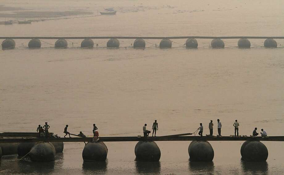 In this Friday, Nov. 16, 2012 photo, Indian laborers work to construct a temporary pontoon bridge over the River Ganges for the upcoming Maha Kumbh festival in Allahabad, India. Millions of Hindu pilgrims are expected to take part in the largest religious congregation on the banks of Sangam, the confluence of rivers Ganges, Yamuna and mythical Saraswati, during the festival in January 2013, which falls every twelfth year. (AP Photo/Rajesh Kumar Singh) Photo: Rajesh Kumar Singh, Associated Press