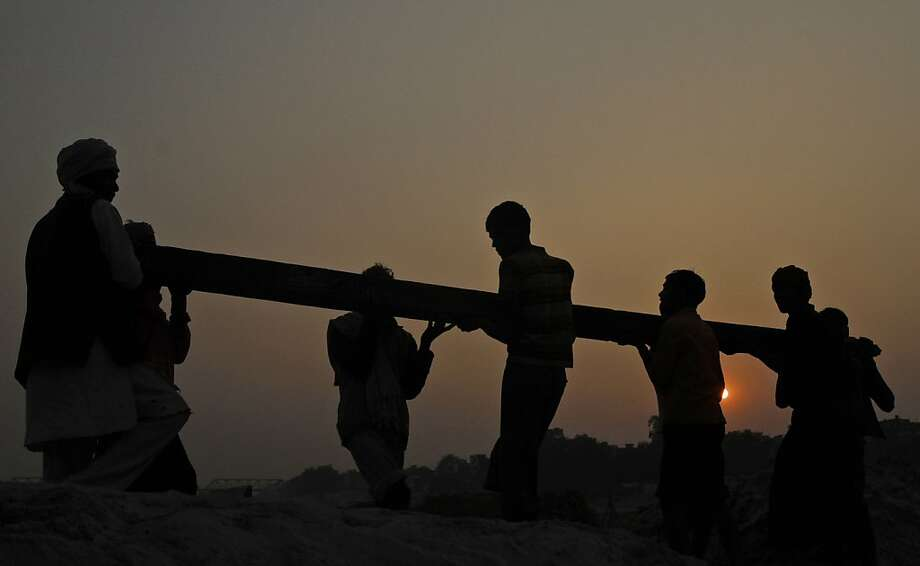 Laborers carry an iron girder to construct a temporary pontoon bridge across the River Ganges for the upcoming Maha Kumbh festival in Allahabad, India, Saturday, Nov. 17, 2012.  Millions of Hindu pilgrims are expected to take part in the largest religious congregation on the banks of Sangam, the confluence of rivers Ganges, Yamuna and mythical Saraswati, during Kumb mela or fair in January 2013, which falls every twelfth year. (AP Photo/Rajesh Kumar Singh) Photo: Rajesh Kumar Singh, Associated Press