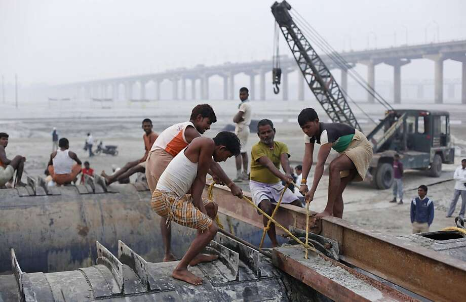 In this Friday, Nov. 16, 2012 photo, Indian laborers work to construct a temporary pontoon bridge over the River Ganges for the upcoming Maha Kumbh festival in Allahabad, India.  Millions of Hindu pilgrims are expected to take part in the largest religious congregation on the banks of Sangam, the confluence of rivers Ganges, Yamuna and mythical Saraswati, during the festival in January, 2013, which falls every 12 years. (AP Photo/Rajesh Kumar Singh) Photo: Rajesh Kumar Singh, Associated Press