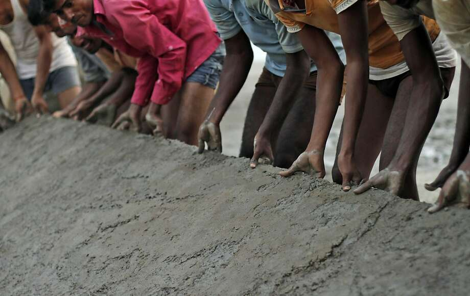 In this Friday, Nov. 16, 2012 photo, Indian laborers carry an iron plate to construct a temporary road on the banks of the River Ganges in preparation of the upcoming Maha Kumbh festival in Allahabad, India.  Millions of Hindu pilgrims are expected to take part in the largest religious congregation on the banks of Sangam, the confluence of rivers Ganges, Yamuna and mythical Saraswati, during the festival in January 2013, which falls every 12 years. (AP Photo/Rajesh Kumar Singh) Photo: Rajesh Kumar Singh, Associated Press