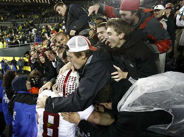Stanford fans mob Stanford quarterback Kevin Hogan after winning their NCAA college football game against Oregon in overtime 17-14 in Eugene, Ore., Saturday, Nov. 17, 2012.(AP Photo/Don Ryan) Photo: Don Ryan, Associated Press