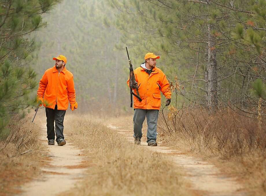 Donnie Kasat, left, and Mike Wagner of Eau Claire, Wis. walk along a trial in the Clark County forest near Fairchild, Wis. while hunting on Saturday, Nov. 17, 2012 during the Wisconsin deer gun season opener.  Photo: Shane Opatz, Associated Press