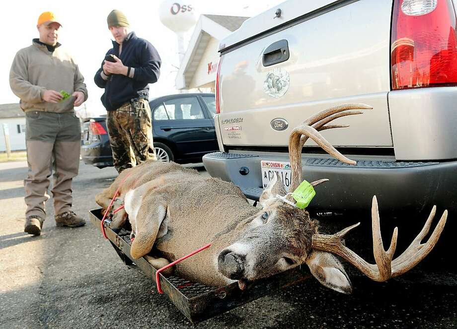 Trever Clark of Burnsville, Minn., left and Derek Hayden of Eau Claire, Wis. register a 12-point buck Clark got on Saturday, Nov. 17, 2012 during the Wisconsin deer gun season opener while hunting near Osseo, Wis. The hunters registered the buck at the Kwik Trip in Osseo, Wis. Photo: Shane Opatz, Associated Press