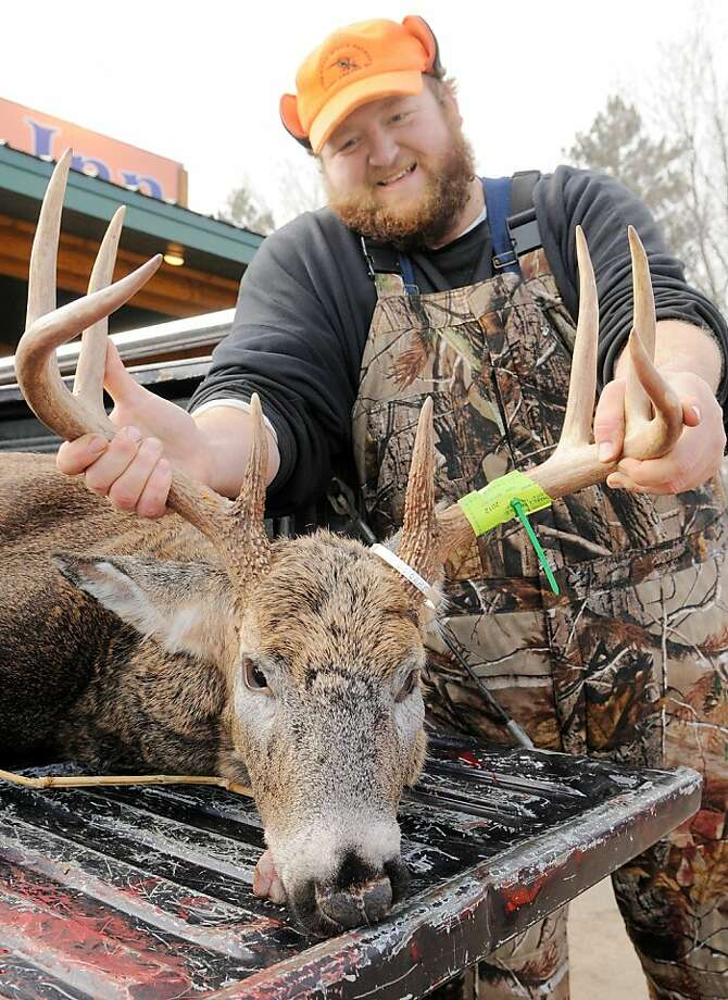 """Mike Prindle of Humbird, Wis. shows off his 8-point buck he shot south of Fairchild, Wis. on Saturday, Nov. 17, 2012 during the Wisconsin deer gun season opener. The buck was big enough to put him in first place on """"Big Buck Bragging Board"""" at the Barrel Inn Bar in Fairchild, Wis. where he stopped to show the owner.  Photo: Shane Opatz, Associated Press"""