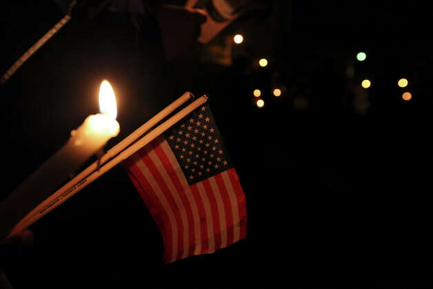 People hold an American flag during a candlelight vigil held at Centennial Plaza in downtown Midland, Tx., Saturday Nov. 17, 2012. The vigil was held to remember people involved in an accident where a Union Pacific train struck a float carrying military veterans,Thursday Nov. 15, 2012, killing four men, including one from the San Antonio area. Photo: Edward A. Ornelas, San Antonio Express-News / © 2012 San Antonio Express-News