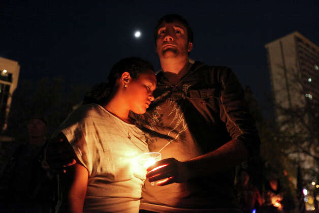 Rebecca and Daniel Young hug while attending a candlelight vigil held at Centennial Plaza, in downtown Midland, Tx., Saturday Nov. 17, 2012, to remember people involved in an accident where a Union Pacific train struck a float carrying military veterans,Thursday Nov. 15, 2012, killing four men, including one from the San Antonio area. Photo: Edward A. Ornelas, San Antonio Express-News / © 2012 San Antonio Express-News
