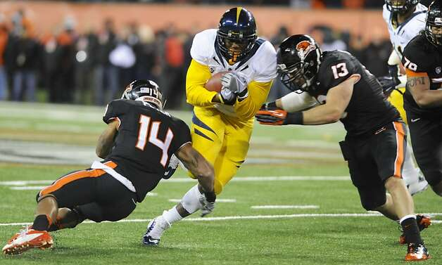 Oregon State's Jordan Poyer (14) and Reuben Robinson (13) tackle against California's C.J. Anderson (9) during the first half of an NCAA college football game in Corvallis, Ore., Saturday Nov.,17, 2012. (AP Photo/Greg Wahl-Stephens) Photo: Greg Wahl-Stephens, Associated Press