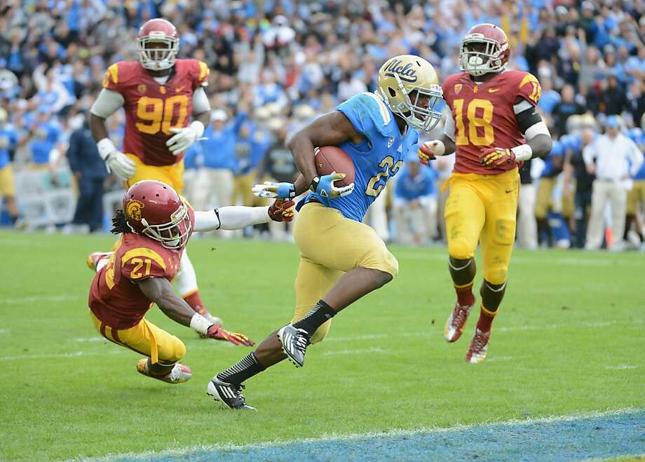 PASADENA, CA - NOVEMBER 17:  Johnathan Franklin #23 of the UCLA Bruins breaks the tackle of Nickell Robey #21 of the USC Trojans to score a touchdown and take a 24-0 lead at Rose Bowl on November 17, 2012 in Pasadena, California.  (Photo by Harry How/Getty Images) Photo: Harry How, Getty Images