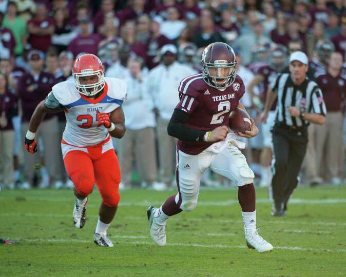 Texas A&M's Johnny Manziel (2) runs around Sam Houston State's Robert Shaw (23) for a touchdown duri