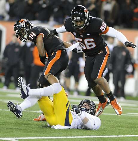 Oregon State's Jordan Poyer (14) and Rusty Fernando (56) break up a pass to California's Chris Harper (6) during the first half of an NCAA college football game in Corvallis, Ore., Saturday Nov.,17, 2012. (AP Photo/Greg Wahl-Stephens) Photo: Greg Wahl-Stephens, Associated Press