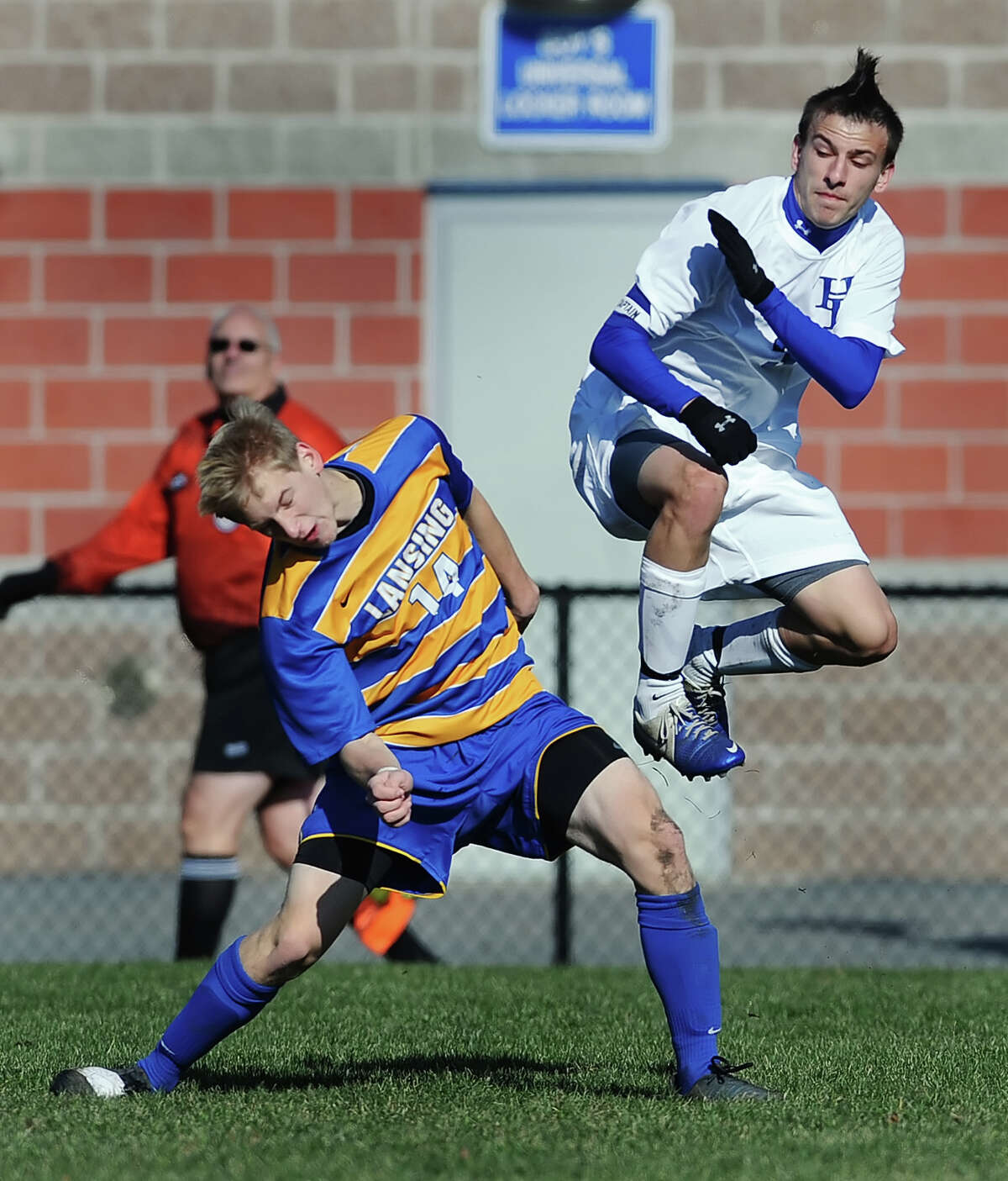 Hoosick Falls' Chris LaCroix, right, braces for impact after clearing the ball by Lansing's Jake Palladino during Class C NYSPHSAA Boys Soccer Championship semifinal played on Saturday, November 17, at Middletown High School.