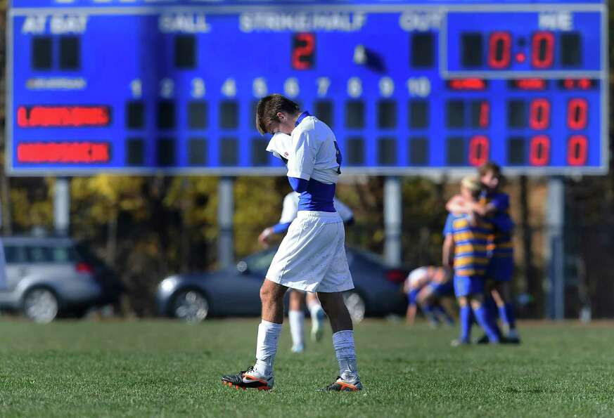 Hoosick Falls' Evan Phillips, center, buries his head in his hands as he walks off the field followi