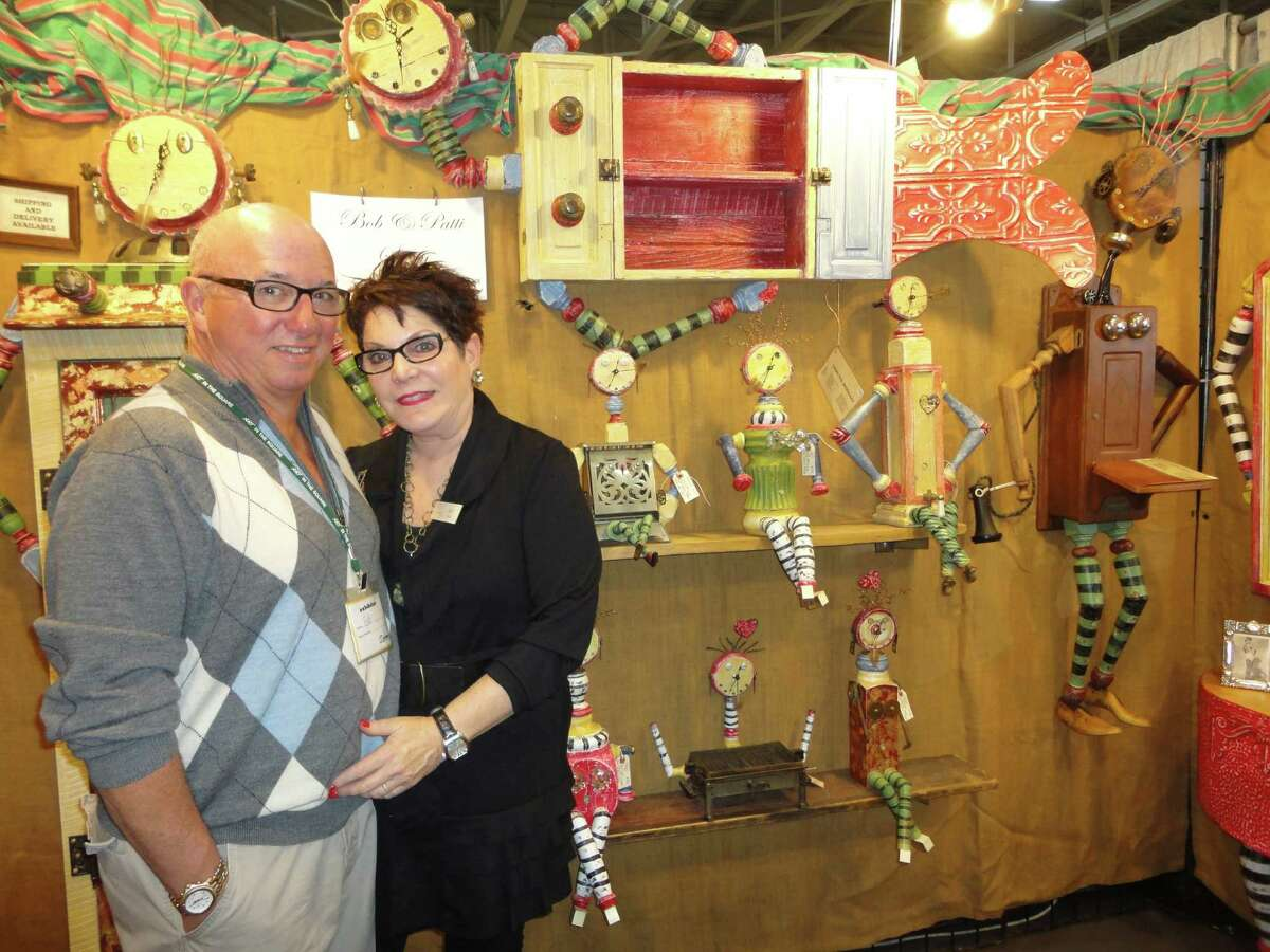 Mixed media artists Bob and Patti Stern of Cleveland, Ohio, pose in front of their whimsical creations Saturday at Staples High School, site of tghe 37th annual CraftWestport. The Sterns are almost the vendors who have appeared most often at CraftWestport. They were participating in their 15th such event. Westport Ct 11/17/12