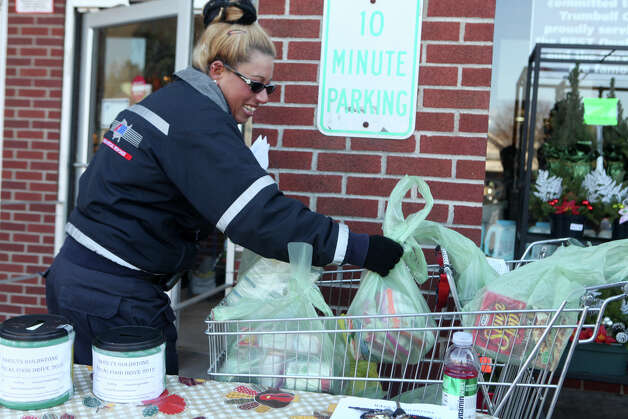 Aimee Roberts, of American Medical Response,  collects food and donations in front of Porricelli's Foods in Trumbull, Conn. on Sunday, November 18, 2012.  The AMR is collecting to benefit the Marilyn Goldstone annual food drive and the Bridgeport Rescue Mission. The donations will feed over five hundred families for Thanksgiving. Photo: BK Angeletti, B.K. Angeletti / Connecticut Post freelance B.K. Angeletti
