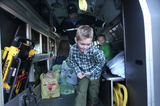 Pat Bridge, of American Medical Response,  lets Mason Maiocco, 6, and his brother Christian, 3, sit in an ambulance while he is collecting food and donations front of Porricelli's Foods in Trumbull, Conn. on Sunday, November 18, 2012.  The AMR is collecting to benefit the Marilyn Goldstone annual food drive and the Bridgeport Rescue Mission. The donations will feed over five hundred families for Thanksgiving. Photo: BK Angeletti, B.K. Angeletti / Connecticut Post freelance B.K. Angeletti