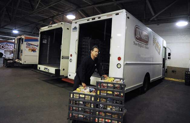 Paul Pierelli of Milford, a driver for Wonderbread for 28 years, unloads his truck at the facility Wells Street in Bridgeport, Conn. on Friday, Nov. 16, 2012. Hostess Brands Inc. announced  itâÄôs going out of business meaning the loss of about 18,500 jobs. Hostess employs about 200 workers in Connecticut in non-bakery retail and distribution facilities. The 50 employees in Bridgeport are caught in a fight between management and The Bakery Confectionery, Tobacco Workers and Grain Millers International Union, which went on strike last week over benefits and the future of the company. Teamsters Local 145, which represents Hostess drivers, mechanics and thrift store employees at its the Bridgeport facility on the corner of Housatonic Avenue and Wells Street in Bridgeport, Conn. Photo: Cathy Zuraw / Connecticut Post