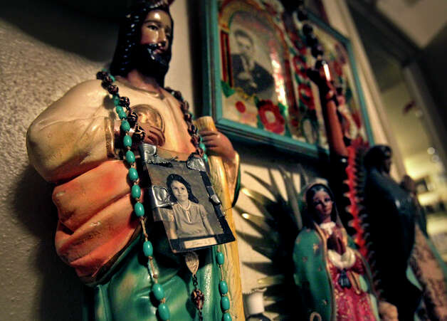 Gloria Herrera has taped a picture of her daughter Elizabeth Ramirez, as a young girl, to a rosary and placed it around a statue of Jesus displayed in a shrine, Friday, Dec. 3, 2010. (Photo by Bob Owen/Express-News) Photo: BOB OWEN, SAN ANTONIO EXPRESS-NEWS / SAN ANTONIO EXPRESS-NEWS