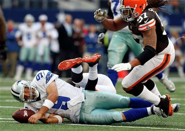 Dallas Cowboys' Tony Romo (9) momentarily loses control of the ball after being brought down by Cleveland Browns' Trevin Wade, center back, and Jabaal Sheard (97) in the second half of an NFL football game on Sunday, Nov. 18, 2012, in Arlington, Texas. Romo recovered the ball. (AP Photo/Sharon Ellman) Photo: Sharon Ellman, Associated Press / FR170032 AP