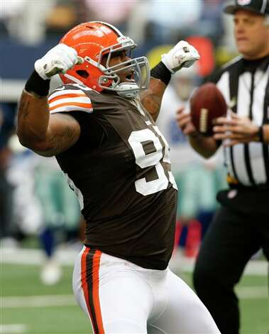 Cleveland Browns' Juqua Parker (95) celebrates sacking Dallas Cowboys quarterback Tony Romo (9) in the first half of an NFL football game Sunday, Nov. 18, 2012 in Arlington, Texas. (AP Photo/Brandon Wade) Photo: Sharon Ellman, Associated Press / FR170032 AP