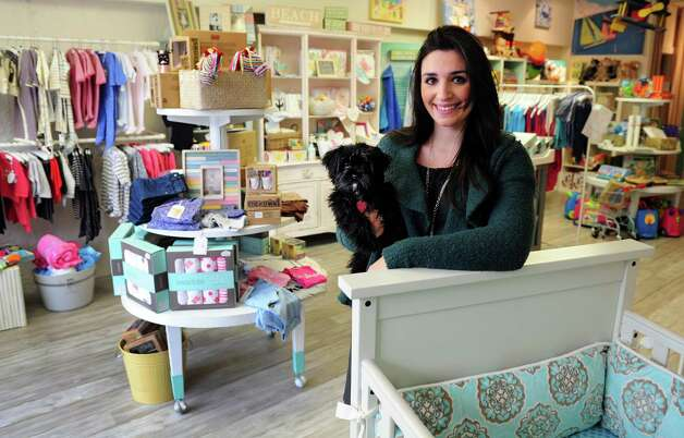 Kara Telep and her dog, Dolce, stand in her brightly colored shop, Baby Love.   The new specialty baby and maternity store recently opened at 113 River Street in Milford. Photo: Autumn Driscoll