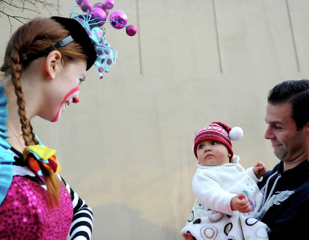 Valerie Lenhart, 10 months, looks unfazed by a juggler on a unicycle as she is held my her father, Eric, during Saturday's Balloon Inflation Party near the intersection of Summer and Hoyt Streets in Stamford on November 17, 2012. Photo: Lindsay Niegelberg / Stamford Advocate