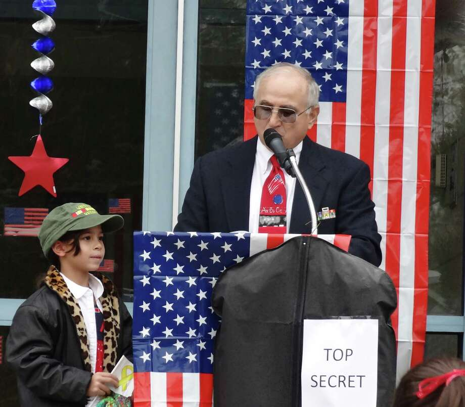 Royal School fifth-grade teacher and U.S. Air Force veteran Joe Squeo reads a Veterans Day poem written by second-grader Victoria Caruso during the school's ceremony. In addition to meeting veterans, students also sang patrioric songs. Photo: Contributed