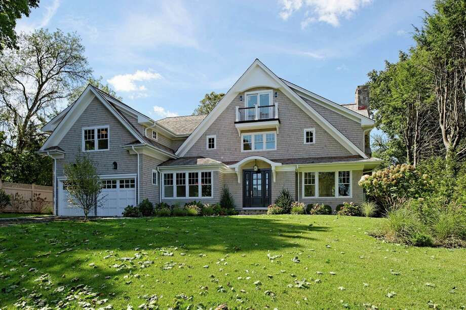 This newly-constructed Nantucket shingle style colonial at 23 Burman Hill was built this year by Bluewater Home Builders on a Compo Beach cul-de-sac. Its exterior amenities include a private, level backyard, an outdoor kitchen for al fresco dining, a stone sitting wall and a fireplace with HDTV wiring above it Photo: Contributed Photo/ Daniel Milste