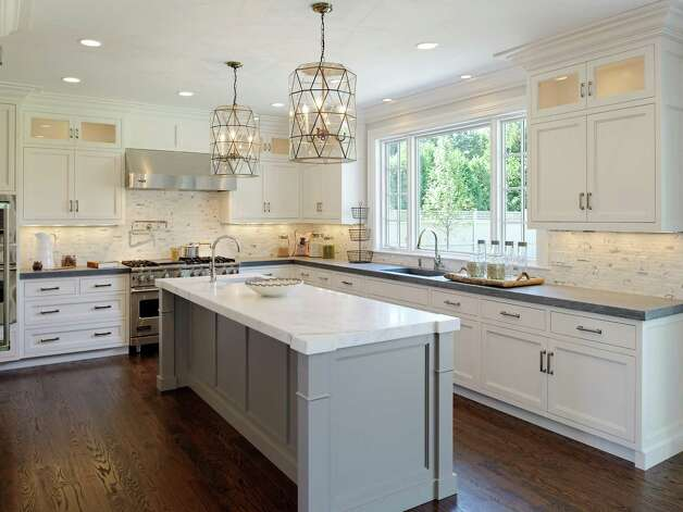 The state-of-the-art, hand-crafted kitchen features custom white cabinetry including a row of illuminated top cabinets, under-cabinet lighting and a breakfast area as well as counters topped in 2-inch thick slab graphite limestone and a large center island surfaced in 2-inch statuary marble. Photo: Contributed Photo/Daniel Milstei / All rights reserved