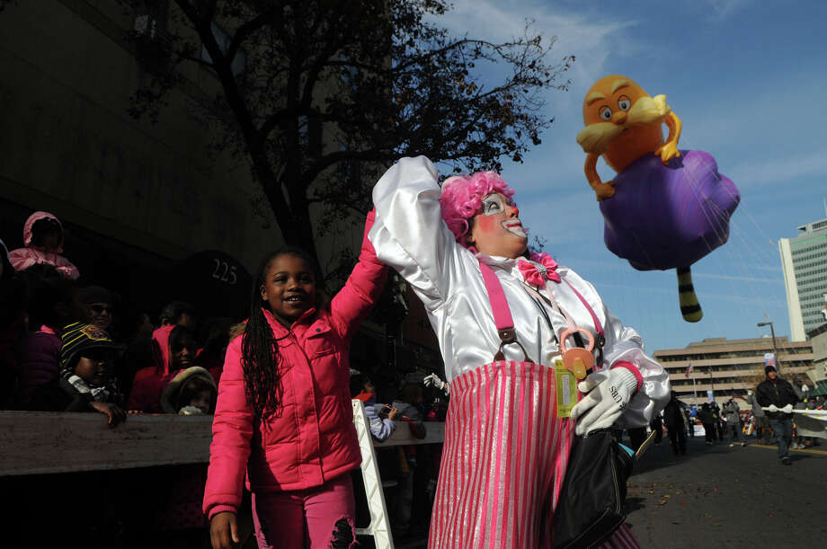 Sanaayh Dotson, 8, dances with a Cirque-tacular clown, played by Barbara Occhino, during the UBS Parade Spectacular in Stamford, Conn., Nov. 18, 2012. Photo: Keelin Daly / Stamford Advocate Freelance