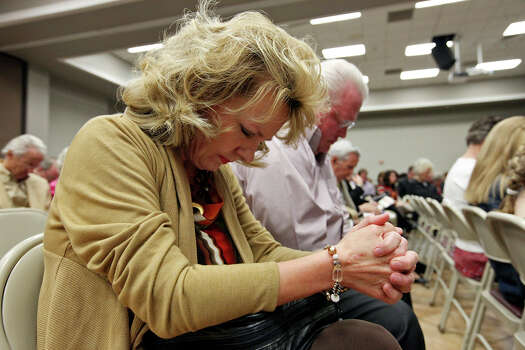 Kimberley and Bobby Norman and others pray for people involved in the Thursday Nov. 15, 2012 accident where a Union Pacific train struck a float carrying military veterans, killing four men, including one from the San Antonio area, during a service at the First Baptist Church Sunday Nov. 18, 2012 in Midland, Tx. Photo: Edward A. Ornelas, San Antonio Express-News / © 2012 San Antonio Express-News