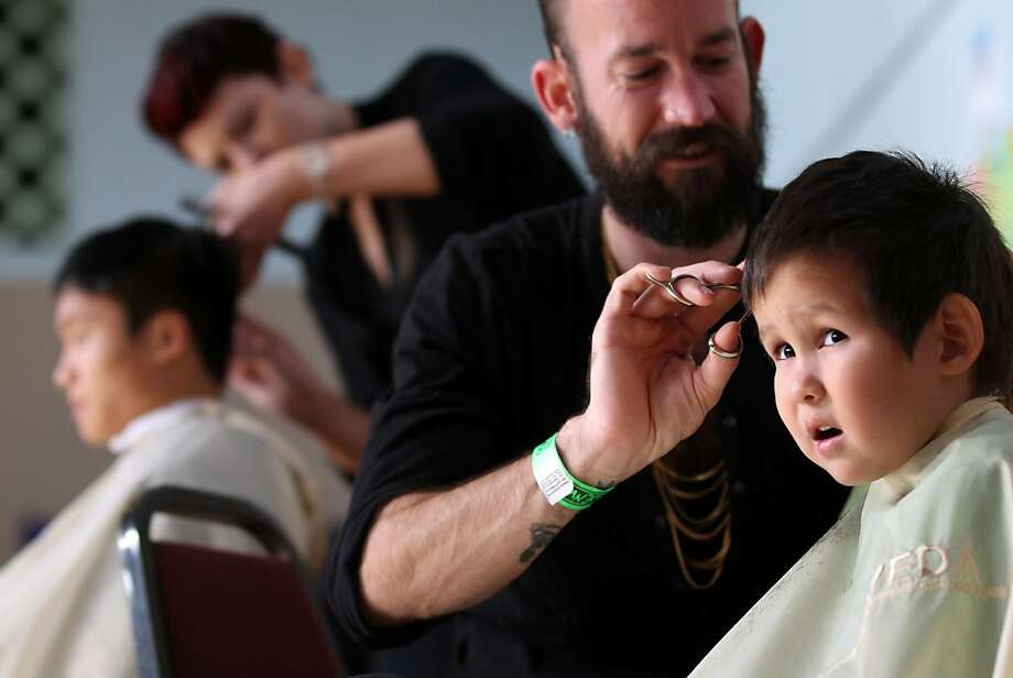 Pavel Arcos, 4, gets a trim from Nikola Zdraljevic, a student from the Cinta Aveda Institute, at Cesar Chavez Elementary School on Sunday. Volunteers gave free cuts to Mission students and their families. Photo: Lance Iversen, The Chronicle