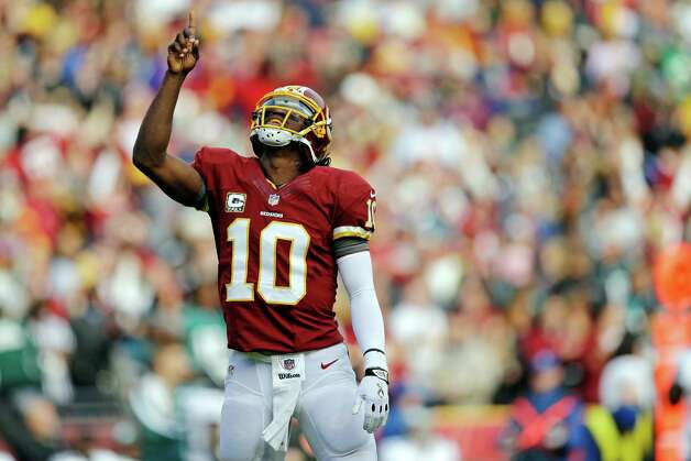 Washington Redskins quarterback Robert Griffin III points toward the sky after throwing a touchdown pass to wide receiver Aldrick Robinson during the first half of an NFL football game against the Philadelphia Eagles in Landover, Md., Sunday, Nov. 18, 2012. (AP Photo/Patrick Semansky) Photo: Patrick Semansky, Associated Press / AP