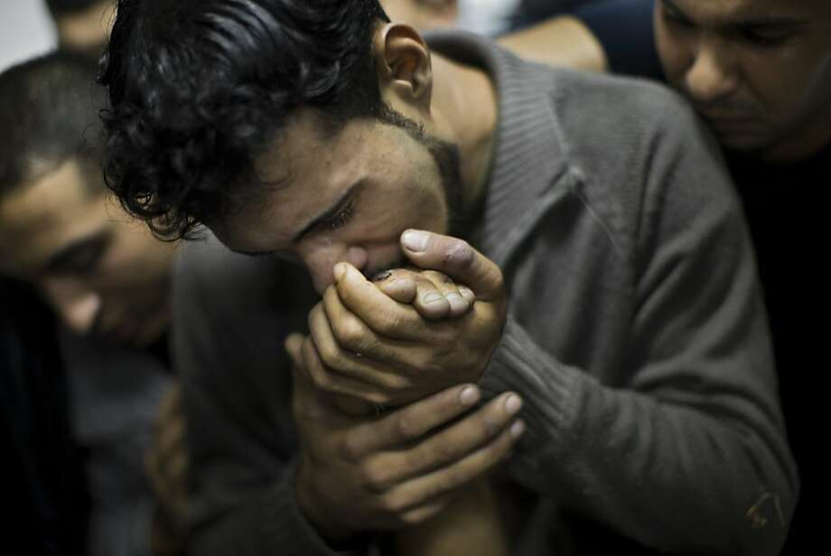 A Palestinian man kisses the hand of a dead relative in the morgue of Shifa Hospital in Gaza City, Sunday, Nov. 18, 2012. President Barack Obama on Sunday defended Israel's airstrikes on the Gaza Strip, but he warned that escalating the offensive with Israeli ground troops could deepen the death toll and undermine any hope of a peace process with the Palestinians. Photo: Majed Hamdan, Associated Press