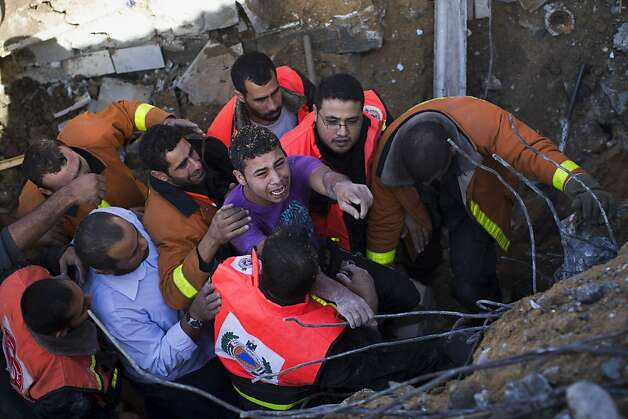 Osama Abdel Aal is rescued after his family house collapsed during an Israeli forces strike in the Tufah neighborhood, Gaza City, Sunday, Nov. 18, 2012. The Israeli military widened its range of targets in the Gaza Strip on Sunday to include the media operations of the Palestinian territory's Hamas rulers, sending its aircraft to attack two buildings used by both Hamas and foreign media outlets. (AP Photo/Bernat Armangue) Photo: Bernat Armangue, Associated Press
