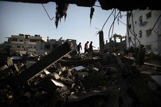 "TOPSHOTS Palestinians salvage for belongings from their destroyed houses following overnight Israeli air strikes on the village of Beit Lahia in the northern Gaza Strip on November 18, 2012. Israeli war planes hit a Gaza City media centre and homes in northern Gaza in the early morning, as the death toll mounted, despite suggestions from Egypt's President Mohamed Morsi that there could be a ""ceasefire soon.""  AFP PHOTO/MARCO LONGARIMARCO LONGARI/AFP/Getty Images Photo: Marco Longari, AFP/Getty Images"