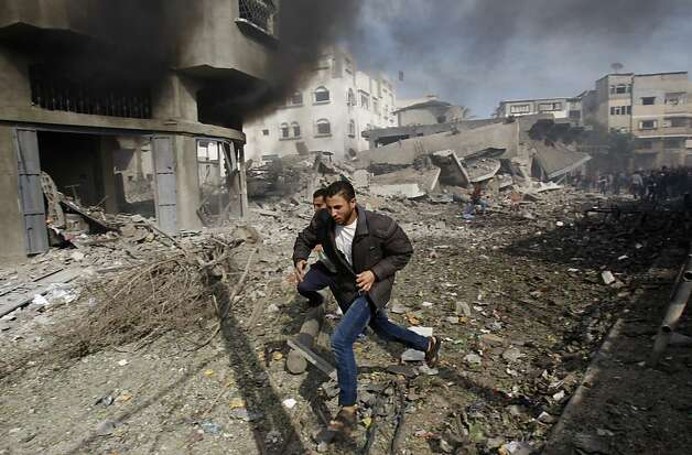 Palestinians run away from a damaged building after an Israeli air strike in Gaza City, Sunday, Nov. 18, 2012. Israel widened the range of targets in its Gaza offensive Sunday, striking more than a dozen homes of suspected Hamas militants and two media offices, according to security officials and witnesses. The attacks also damaged adjacent houses, killing seven civilians, including five children, health officials said.  (AP Photo/Adel Hana) Photo: Adel Hana, Associated Press