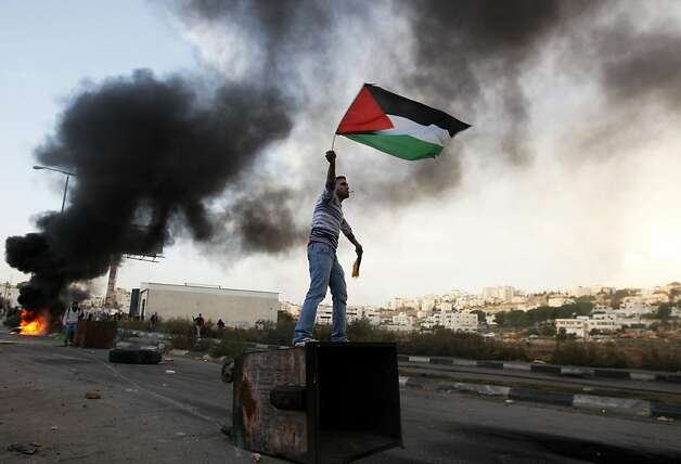 A Palestinian man waves national flag during a protest against Israel's operations in Gaza Strip, outside Ofer, an Israeli military prison near the West Bank city of Ramallah, Sunday, Nov. 18, 2012. (AP Photo/Majdi Mohammed) Photo: Majdi Mohammed, Associated Press