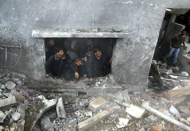 Palestinians search the debris of the al-Dallu family home following an Israeli air strike in Gaza City, on November 18, 2012.  At least seven members of the same family, including four children, were among nine people killed when an Israeli missile struck a family home in Gaza City, the health ministry said.  AFP PHOTO/MAHMUD HAMSMAHMUD HAMS/AFP/Getty Images Photo: Mahmud Hams, AFP/Getty Images