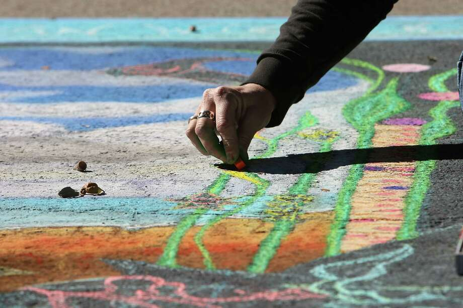 An artist works on a chalk art piece during the Via Colori Street Chalk Art Festival in downtown Nov. 18, 2012, in Houston. Photo: James Nielsen, Chronicle / © Houston Chronicle 2012