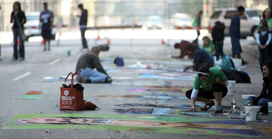 Artist work on chalk art pieces during the Via Colori Street Chalk Art Festival in downtown Nov. 18, 2012, in Houston. Photo: James Nielsen, Chronicle / © Houston Chronicle 2012