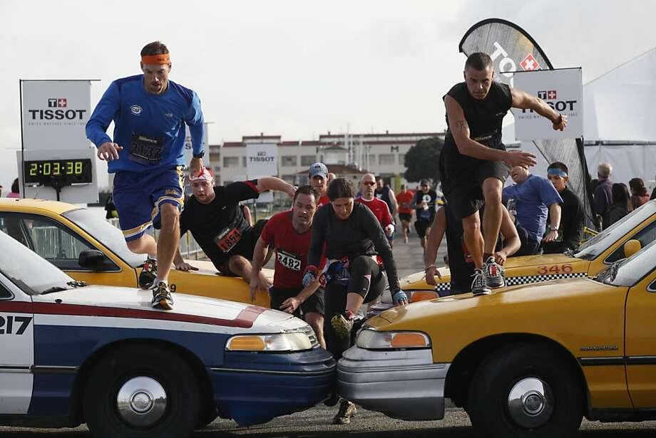Racers scramble over taxis, one of the many types of obstacles, near the end of the 10.2-mile Men's Health Urbanathlon in S.F. Photo: Alex Washburn, Special To The Chronicle