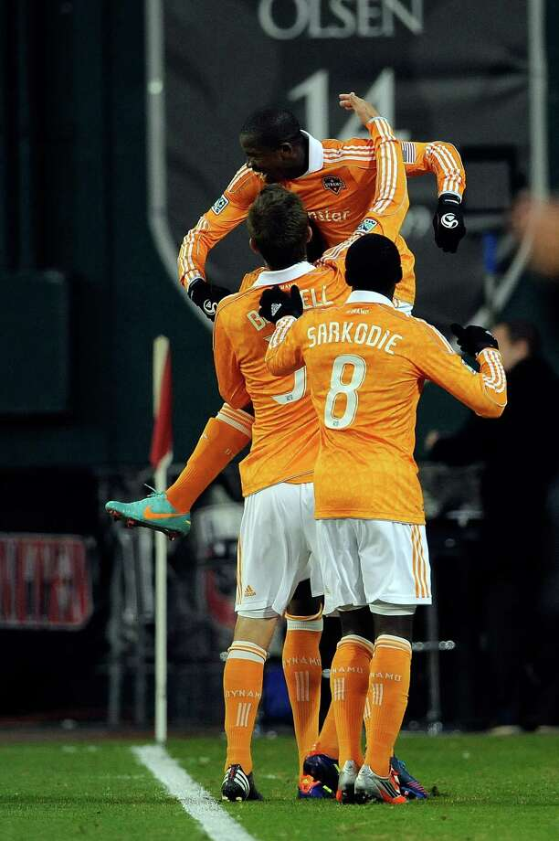 Dynamo players Boniek Garcia celebrates with Kofi Sarkodie #8 and Bobby Boswell #32 of Houston Dynamo after scoring a goal against D.C. United.  Photo: Patrick McDermott, Getty Images / 2012 Getty Images