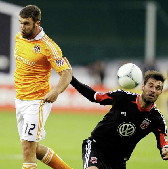 Will Bruin (12) and DC United's Emiliano Dudar, right, try to head the ball.