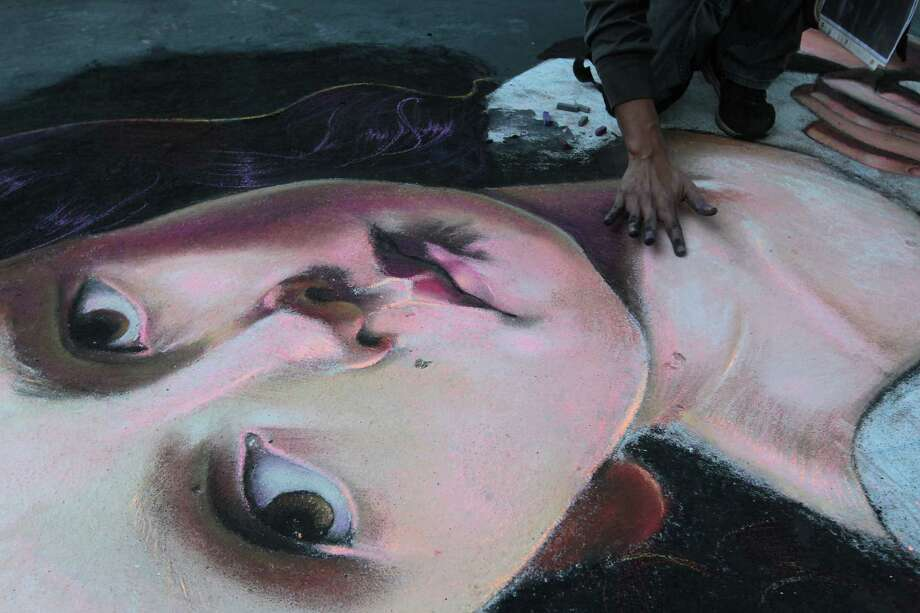 """Ever Galvez works on his chalk art piece titled """"The Prayer"""" during the Via Colori street chalk art festival in downtown Nov. 18, 2012, in Houston. Photo: James Nielsen, Chronicle / © Houston Chronicle 2012"""