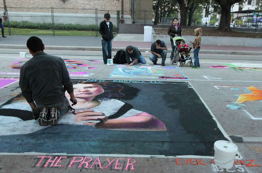 "Ever Galvez left, works on his chalk art piece titled ""The Prayer"" during the Via Colori street chalk art festival in downtown Nov. 18, 2012, in Houston. Photo: James Nielsen, Chronicle / © Houston Chronicle 2012"