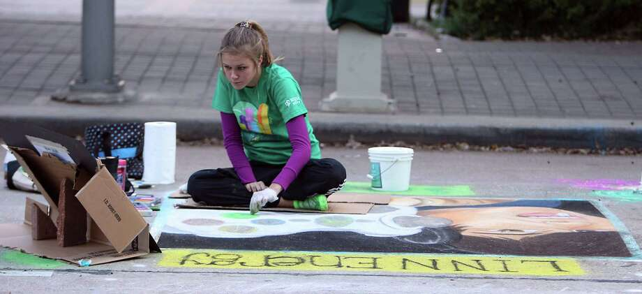 "Brooke Scrutchin works on her chalk art pice titled ""Generation Technology"" during the Via Colori street chalk art festival in downtown Nov. 18, 2012, in Houston. Photo: James Nielsen, Chronicle / © Houston Chronicle 2012"