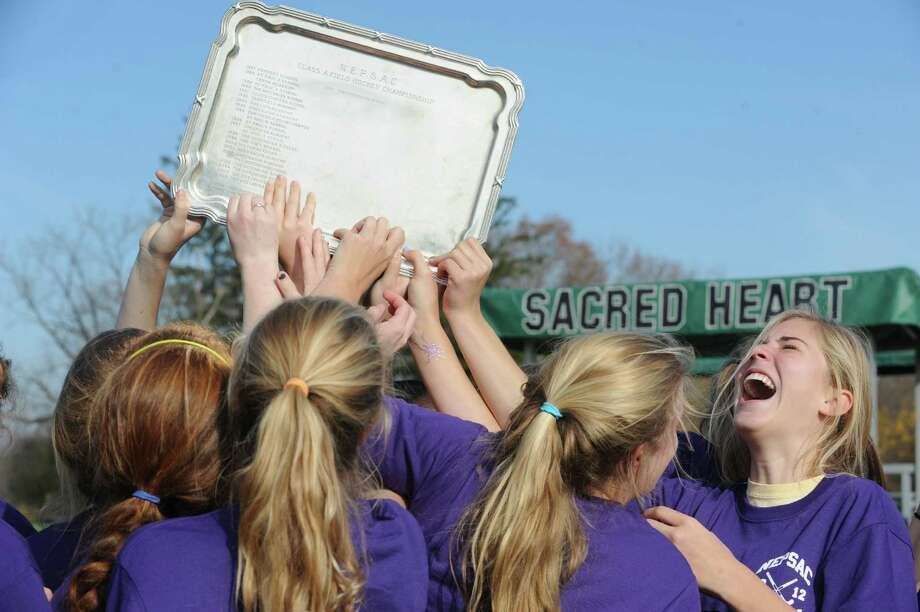 Izzy Nixon, right, celebrates with her teammates as they hold the championship trophy after Greenwich Academy won the NEPSAC Class A field hockey title on Sunday at Convent of the Sacred Heart. Photo: Helen Neafsey