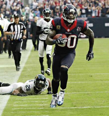 HOUSTON, TX - NOVEMBER 18:  Andre Johnson #80 of the Houston Texans scores on a 48 yard reception in overtime against the Jacksonville Jaguars as Dawan Landry #26 of the Jacksonville Jaguars watches at Reliant Stadium on November 18, 2012 in Houston, Texas. Houston won 43-37 in overtime. Photo: Bob Levey, Getty Images / 2012 Getty Images